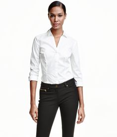 Hvit. En langermet, figursydd skjorte i elastisk kvalitet. Skjorten er v-utringet og har knapping foran og nederst på ermene.