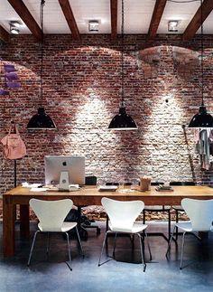Me encantan las paredes de obra vista! Genial el juego de luces y la combinación de madera con techo y sillas blancas