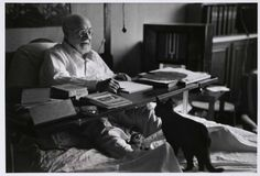 Henri Matisse in bed working, his black cat at his feet, (Cimiez) Nice, France, August 1949 by Robert Capa.