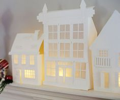 Free Printables: Illuminated Mantle Village Get these templates FREE! Via Country Home. They used card stock for the buildings and added waxed paper behind the windows to create the village. Add lights on the inside to make the village truly festive.