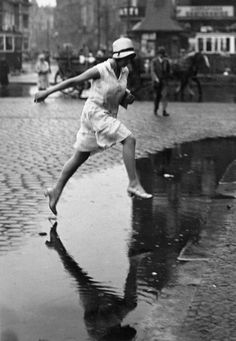 Puddle jumping to drier sidewalks. c 1930s