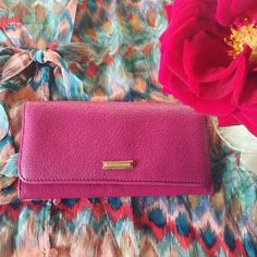 """Burberry Grainy Leather Fuschia Continental Wallet In great pre-love condition! No tears, wears on corners ( see pic 4 ) Smooth, topstitched leather trim is beautifully juxtaposed against the pebbled leather of a chic flap wallet  accented with Burberry print jacquard lining. Calf leather with cow leather trim Front snap flap closure Slip pocket at the back Interior zip coin pocket 4.5""""H x 7.5""""L x 1.5""""D 16 credit card slots Dollar bill pockets Burberry print jacquard lining Burberry Bags…"""