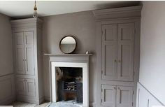love this, 2 integrated armoires painted grayish prune like wall, one on each side of bedroom fireplace