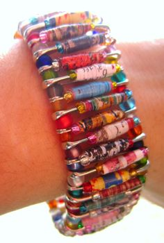 Combines the idea of paper beads with the safety pin bracelet Really cute! Project for camp?