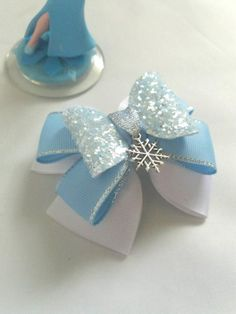 Elsa, Frozen inspired pinwheel style layered hair bow made with white grosgrain ribbon, blue grosgrain ribbon with silver edging, ice blue glitter fabric with silver or white snowflake centre piece, please select your snowflake colour preference Elsa Frozen Hair, Frozen Hair Bows, Elsa Hair, Disney Hair Bows, Frozen Headband, Frozen Queen, Frozen Princess, Princess Hair Bows, Girl Hair Bows