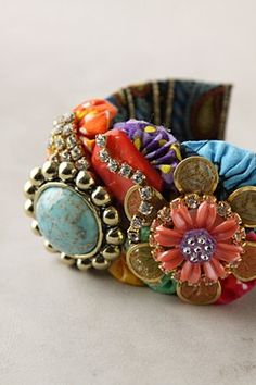 """Brightly printed African-inspired fabric tucks around a wide bracelet, as rhinestone chains and mesh and resin petals gather on top.      Glass, mother-of-pearl, Swarovski crystal, resin, brass, plastic, polyester     1.75""""W, 2.5"""" diameter Anthropologie, I love you."""