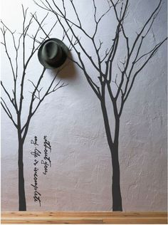 Painted tree silhouettes on wall fit with hooks for hats & coats - beautiful and it doesn´t take much space