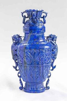 CHINESE CARVED LAPIS LAZULI ARCHAIC VASE , the tapering baluster body with fanciful cover carved with a coup and fitted with four loose rings, the tapered baluster body with dragons at each side, the body decorated with stylized butterflies, flora and fauna. height 10 in., width 3 in.