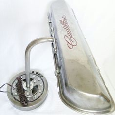 This unique desk lamp features a vintage steel Cadillac script valve cover mounted on a harmonic balancer base. Constructed from used engine components, which have been cleaned with solvents, grinded