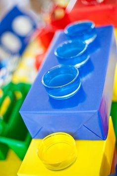 Cover a tissue box with wrapping paper, cut a few holes, and put plastic cups in them. | How To Throw The Ultimate LEGO Birthday Party