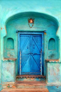 Cobalt blue door in turquoise wall, location not identified, but i would guess…