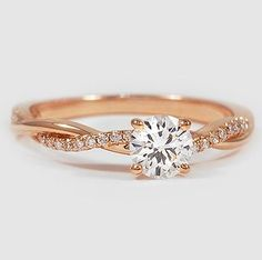 This beautiful ring features a strand of diamonds entwined with a high polished ribbon of rose gold.