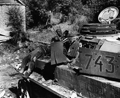 Dead Germans sprawled on a tank in northwest Europe, circa 1944. Tanks protect you from the usual missiles, but when they go up in flames there's no escape.