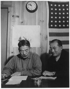 Adams' images capture the social order to life at the camp. Here, Manzanar resident Roy Takeno (right) sits next to the mayor.