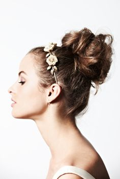 """THE HEIRESS Bright, playful, and the look most closely resembling a traditional up-do, this one makes a fine counterpart to the Regal Promenade Headband (and ballroom reception). Moiz began by setting the entire head with a 1-inch barrel curling iron. After combing it out, he gathered a high ponytail on top of the head. He then began pinning sections of hair around the base of the pony—""""it gets more artistic as you play with it,"""" he said."""
