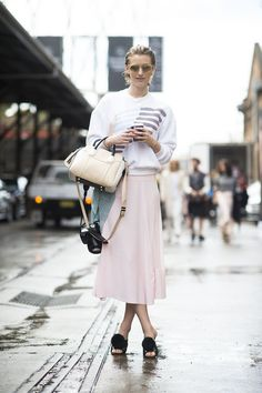 Sporty-cum-girlie when a sweatshirt meets a petal-pink skirt and pom-pom adorned mules. Sydney Fashion Week #StreetStyle                                                                                               20 / 51
