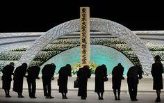 Familieleden van slachtoffers van de aardbeving en tsunami op 11 maart 2011 maken een buiging voor het altaar en bieden  chrysanten aan.