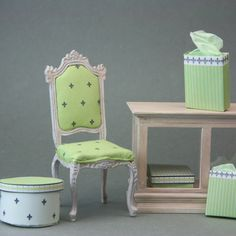 A dolls house chair has been upholstered to match miniature shop fittings, paint and drapes.