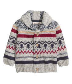 En jacquardstickad cardigan i bomullsblandad kvalitet med inslag av ull. Den har sjalkrage och knäppning fram. Ribbstickad mudd vid ärmslut samt nedtill.
