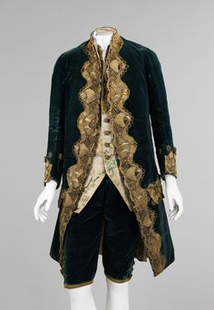 An example of a mens dress coat with matching breeches and vest. The coat and the breeches are made of the same material, this looks to be velvet and the vest is an embroidered fabric in a class rococo style print of pale colors and often a floral print. Gold lace edge the jacket front, sleeves, and pockets with covered buttons down the front and at the hem of the breeches. The only thing missing to complete this outfit would be a jabot at the neck.