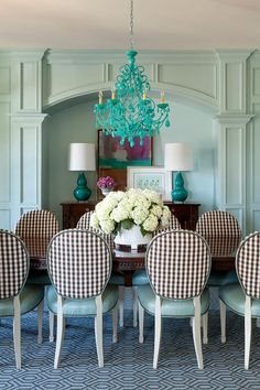 Chairs by Hickory Chair Furniture sit on a brown and blue geometric rug flanking an antique dining table lit by a Canopy Designs Beach Florentine Chandelier.