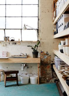 Simple, Worn Studio Interior with Exposed Brickwork and Wooden Shelves