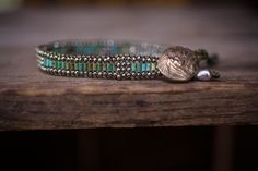 A woven strap filled with warming Turquoise Heishe  beads paired with faceted Pyrite.  Enhanced with a golden bronze Plains Indian button closure.
