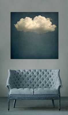 Gorgeous cloud painting sitting above a stylish couch.