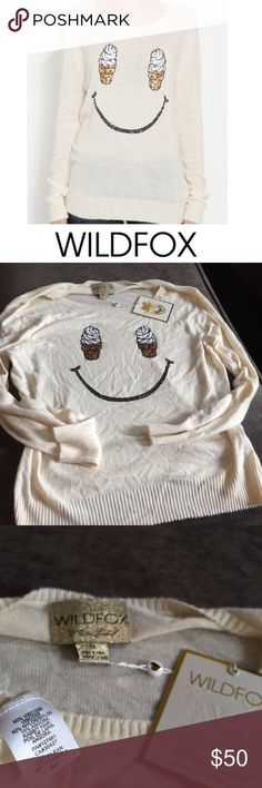 WildFox Cream Ice Cream Cone Smile Sweater WildFox Cream Ice Cream Cone Smile Sweater.  Oversized style. 25 inch bust. 30 inches long. Long sleeve. Cones and smile made of sequins. Light weight, you can see from the model, the fabric is light, because her black jeans show a bit. New with tags. No flaws or stains. Feel free to make an offer. Wildfox Sweaters Crew & Scoop Necks