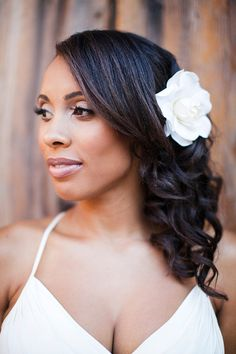 Wedding hair with loose curls and a flower clip.