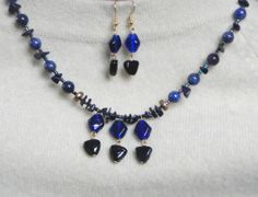 Blue glass diamonds & black glass triangle beads meet dark blue goldstone chips. Its a match with Lapis Lazuli round and shiny tube beads   $36.00