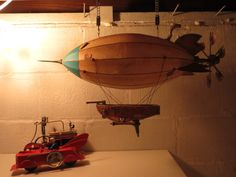 Photo of an Artsmith Craftworks steampunk airship hanging in its dispay position in its new owner's home.