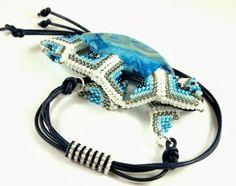 """Naszyjnik """"Niesforne trójkąty"""". W sercu błękitny agat koronkowy, otoczony koralikami toho, wykończony srebrnymi ogniwkami i naturalnym rzemieniem."""