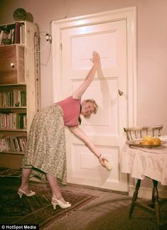 A 1957 housewife multitasks by cleaning the doors while performing her daily stretches, left, and who needs a skipping rope or an aerobics step when you can improvise with a potato masher? Yoga History, Daily Stretches, Old Lady Humor, Vintage Photos Women, Vintage Photographs, Card Workout, Mother Photos, Yoga World, Vintage Housewife