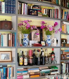 Book shelves- near center shelf place two small arrangements of fushia peonies  and a picture behind them in a gold frame.