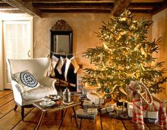 Decked out in shades of gold, white, and blue, van Breems's Christmas tree shines in the living room. The armchair dates from the 1930s. Van Breems found the 19th-century child's table and antique ebonized mirror in Sweden. - CountryLiving.com