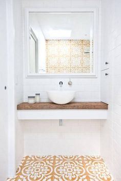 Love this small bathroom design with floating white counter topped with unfinished reclaimed wood counter top, small white basin sink, wall-mounted silver sink faucet, and gorgeous dark yellow, tan and white printed Spanish-inspired tiles on the floor and Bathroom Renos, Laundry In Bathroom, Bathroom Interior, Bathroom Ideas, Bathroom Styling, Bathroom Storage, Tiny Bathrooms, Counter Top Sink Bathroom, Modern Bathrooms