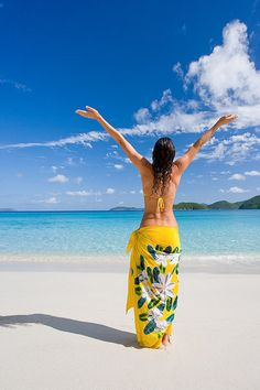 ....female on beach with tropical sarong and arms outstreached feeling happy and free in caribbean island