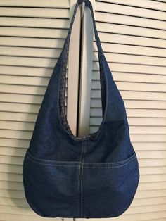 Denim hobo bag is 22 over all with strap. Body of bag is 10 x15 wide and has 2 front outside pockets. Lined inside with zipper pocket on one side and open pocket on the other. Magnetic snap closure.