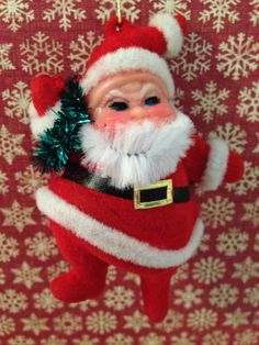 This listing is for one vintage Santa ornament. The Santa is holding a wreath and is in good condition for his age. He is about 3 1/2 in tall and