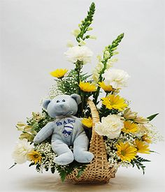 It's a Boy Bouquet  This adorable baby boy arrangement is designed in a natural wicker basket using white Snapdragons, white Carnations, white Daisies, yellow Chrysanthemums, yellow Alstroemeria and delicate Babys Breath and accented with a soft plush blue Teddy Bear. $49.95