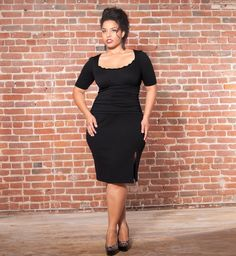 Dangerous curves ahead. The knit fabric hugs your curves creating a sultry silhouette.  A side slit reveals a hint of skin while dainty lace at the neckline adds a hint of sweetness.  Dollface Dress by Kiyonna in Black Noir #plussize