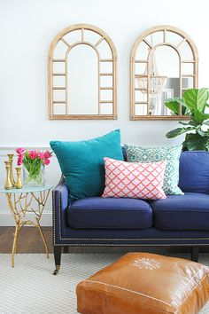 living room with navy sofa, colorful pillows for spring, and a DIY leather pouf