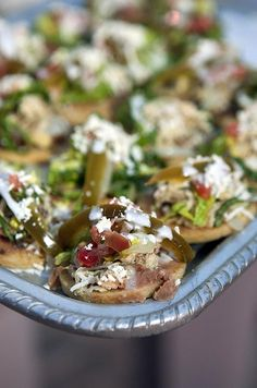 Mexican-inspired hors d'oeuvres, such as these chicken sopes with huitlacoche sauce, are passed on silver trays.