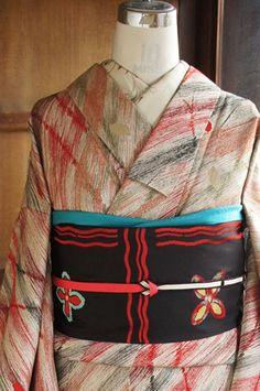 アッシュベージュの地に、クレパスで描いたような黒と赤の斜めストライプが大胆に織り出され、木の葉揺れる木立模様が浮かび上がるモダンデザインが印象的な袷着物です。