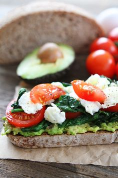 Avocado Toast with Eggs, Spinach, and Tomatoes Recipe on twopeasandtheirpod.com This simple and healthy avocado toast is my go to meal! It is so easy and SO good!