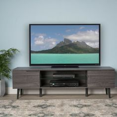 This TV stand is ideal for any living room. Glass meets wood in perfect harmony with this stand. With a glass shelf and wire holes on the back of this unit, you will have a stylish, clutter free TV area, allowing both you and your guests to focus on what's on the screen, rather than what's below it. With a 3D paper veneer finish, not only is this TV stand easy to maintain and clean, but it will have a natural wood grain finish to boot, giving you the optimal look for your living room. This…