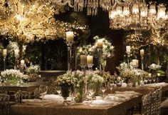 Wedding decorated with white flowers, chandeliers, string lights, crystal sousplat, acrylic chairs and candles