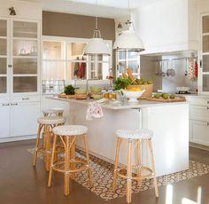 Cocina blanca con isla sobre suelo hidraulico y taburetes de fibras_00379036