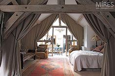 Combles aménagés en chambre avec d'épais rideaux pour séparer les espaces